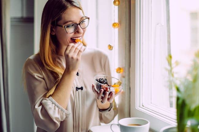 photo of woman eating dried fruit