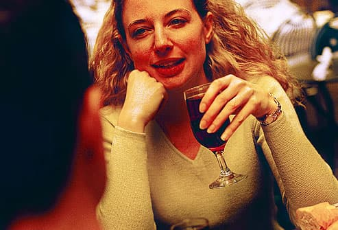 young woman holding full glass of red wine