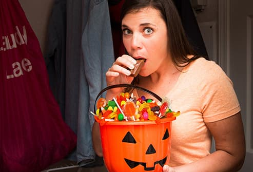 woman sneaking halloween candy in closet
