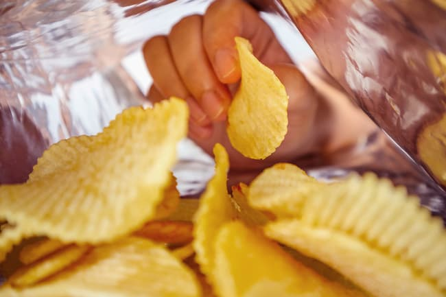 photo of hand in bag of chips