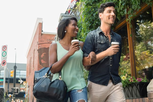 photo of couple walking with coffee