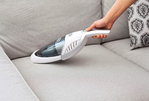 woman vacuuming sofa cushion