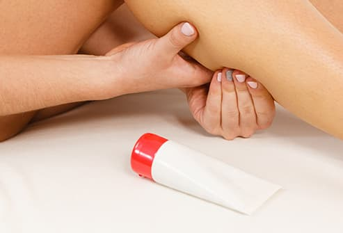 woman massaging cream into calf