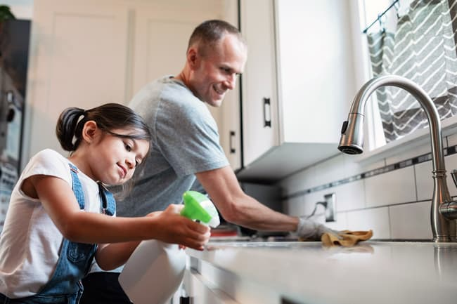 photo of father and daughter clearing countertop