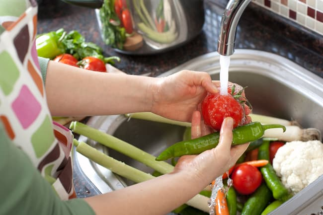 photo of woman washing vegetables