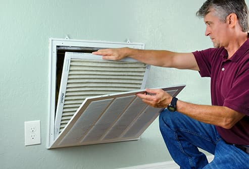 man changing air filter in ac unit