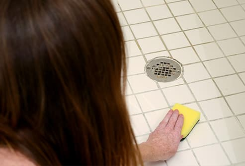 woman scrubbing bathroom floor