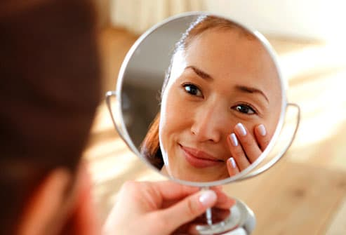 Woman checking for dry skin in mirror