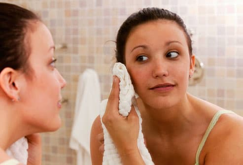 Woman patting face dry with towel
