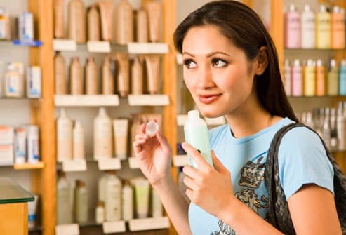Woman sniffing cleanser in cosmetics section