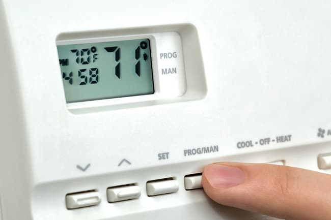 finger on thermostat