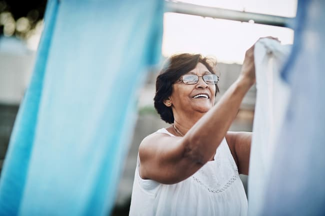 photo of woman hanging laundry outside