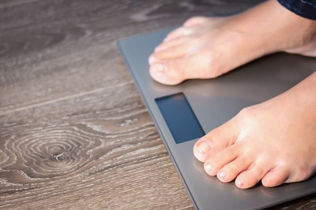 mans feet on home weight scale
