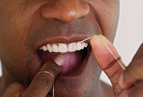 man flossing his teeth close up