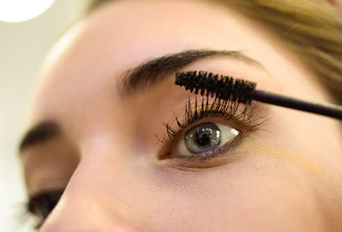 woman applying mascara close up