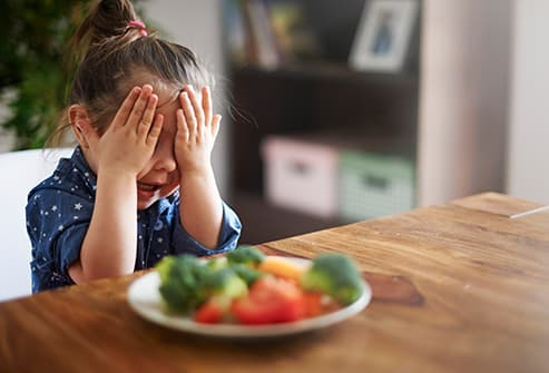 little girl disgusted by vegetables