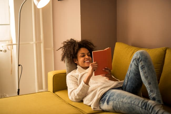 photo of woman on couch reading book
