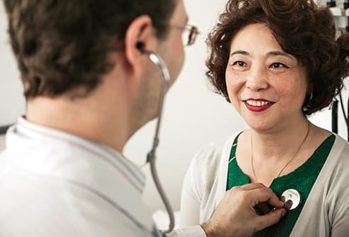 doctor checking heartbeat of mature woman