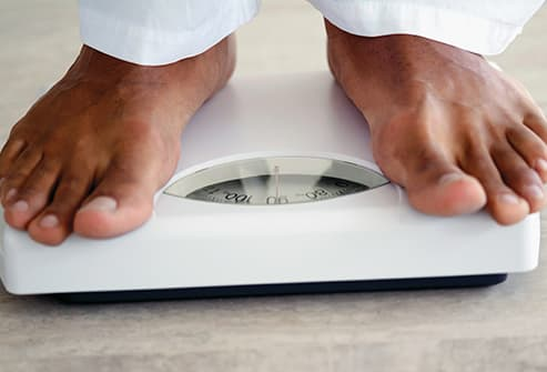 man checking weight on scale