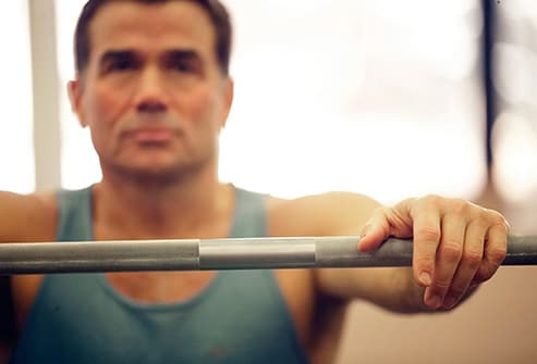 man resting on weight bar