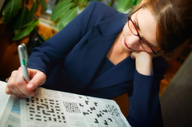 woman working crossword puzzle