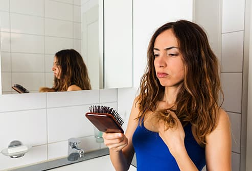 woman looking at hair ends