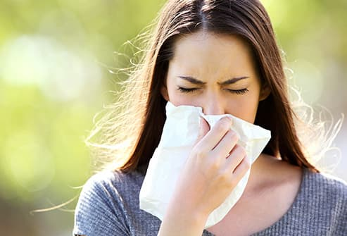 woman outdoors with allergies