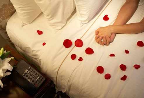 Couples clasped hands on bed covered with roses