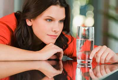 Woman contemplating water glass as half full