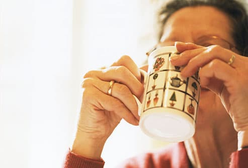 Mature woman drinking hot drink, close-up