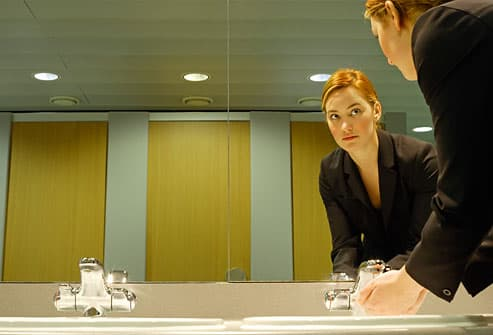 Young businesswoman washing hands in bathroom