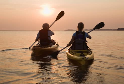 Couple Kayaking Into Sunset