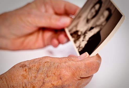 senior woman holding old photo