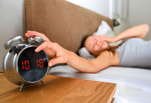 Woman silencing alarm clock late in the day