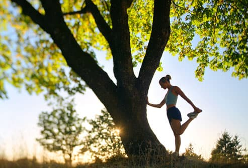 Woman jogger stretching against a tree at sunrise