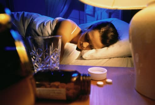Woman asleep with sleeping pills nearby