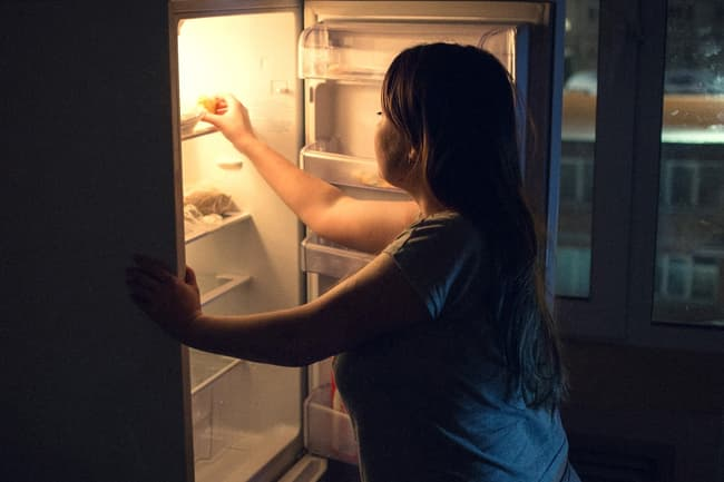 photo of woman snacking at night