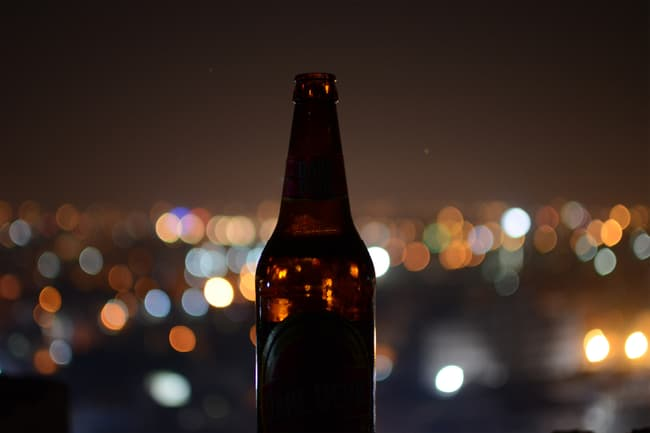 photo of beer bottle at night
