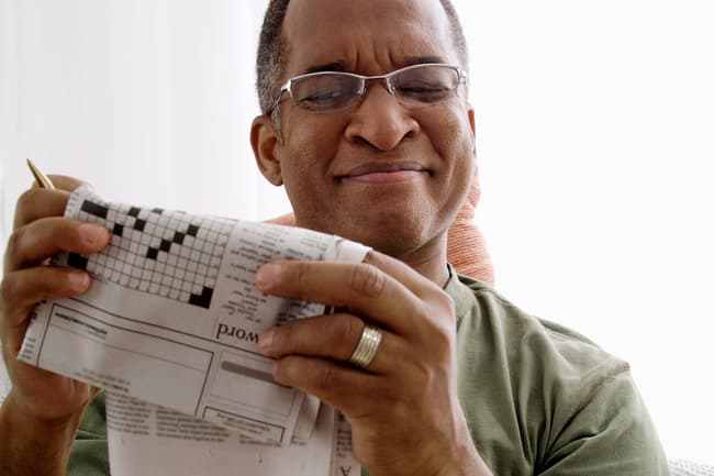 photo of man doing crossword puzzle