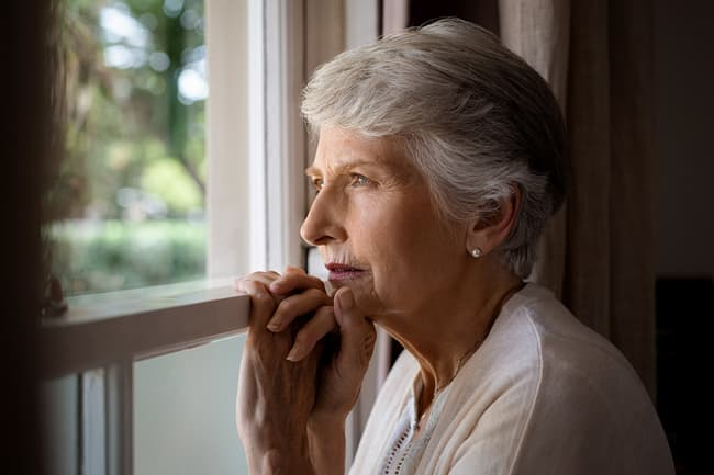 photo of mature woman looking out of window