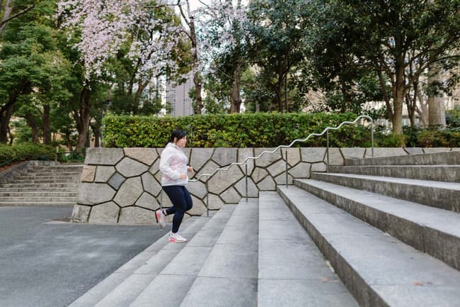 photo of woman running up steps