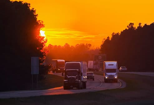 Trucks on highway at sunset