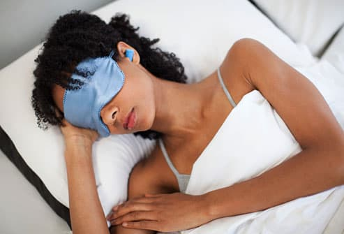 Woman sleeping in eye mask and ear plugs