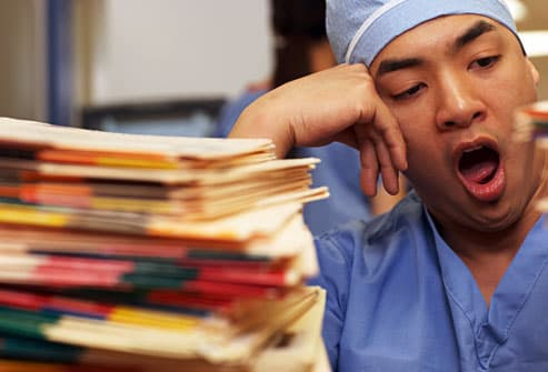 Nurse yawning over huge stack of paperwork