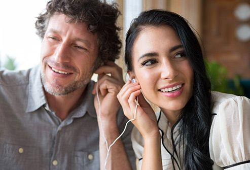 couple listening to music with earbuds