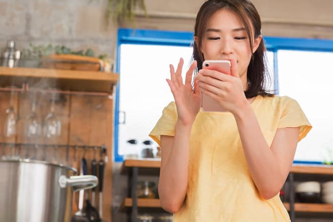photo of woman using smartphone in kitchen