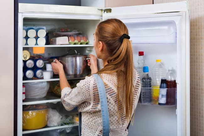 photo of person storing pot in fridge
