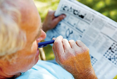 senior man working crossword