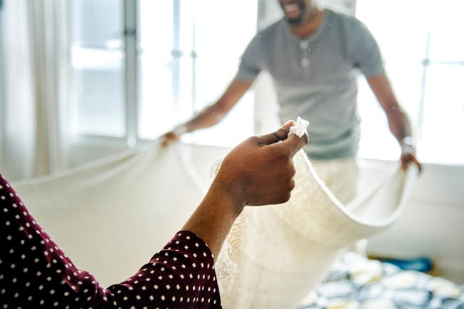 photo of couple making bed