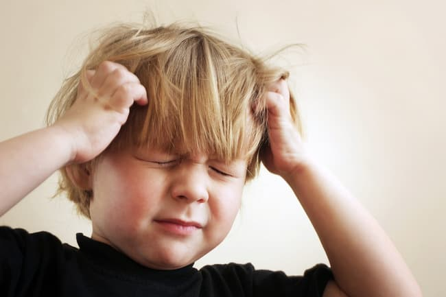 photo of young boy scratching his head